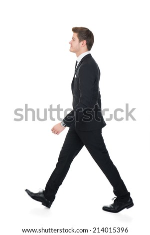 Full length side view of confident businessman walking against white background - stock photo