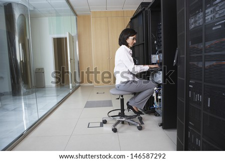 Full length side view of female technician working in server room