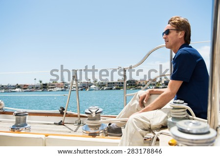 Full-length side view of man sitting on yacht - stock photo