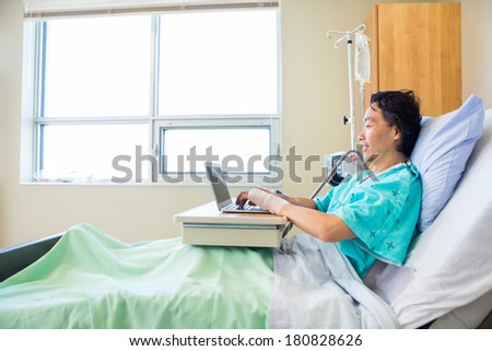 Full length side view of mature male patient using laptop on bed in hospital - stock photo