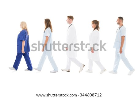 Full length side view of medical professionals walking in row against white background - stock photo
