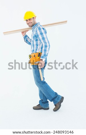 Full length side view of smiling worker carrying wooden planks over white background - stock photo