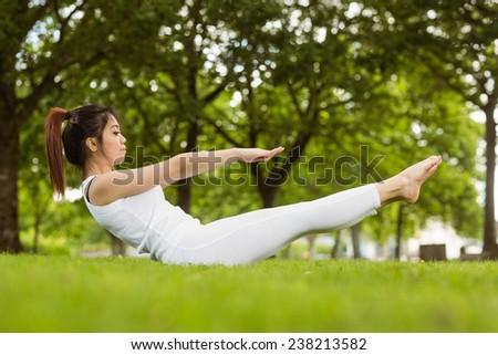 Full length side view of toned young woman doing the boat pose in park - stock photo