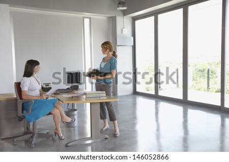 Full length side view of two female executives talking at desk in empty office - stock photo