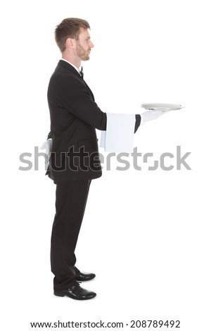 Full length side view of waiter holding empty tray isolated over white background