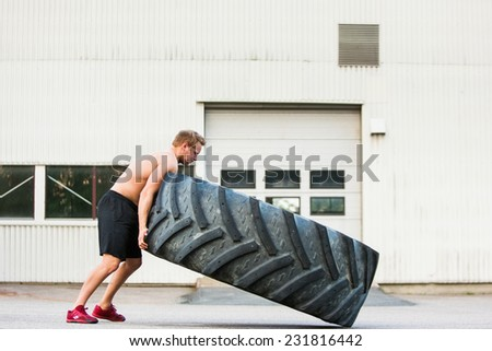 Full length side view of young male athlete flipping large tire outside gym - stock photo