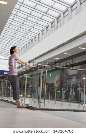 Full length side view of young woman leaning off railing in shopping centre - stock photo