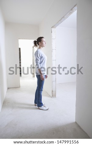 Full length side view of young woman standing in hallway of new apartment - stock photo