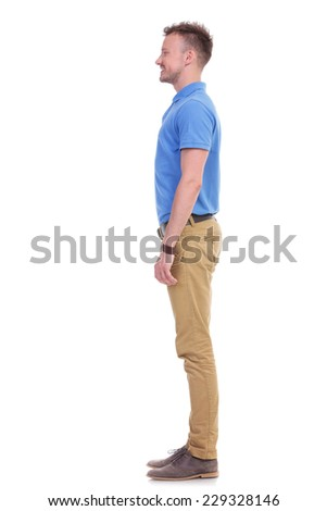 full length side view picture of a young casual man smiling while looking forward. isolated on a white background - stock photo