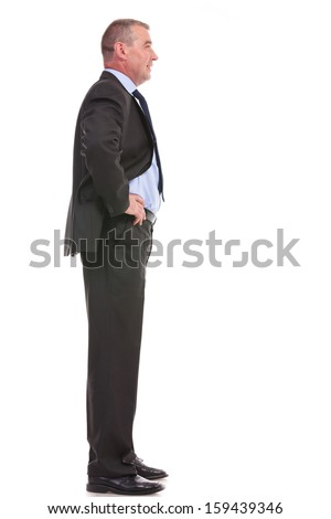 full length side view portrait of a business man standing with his hands on his hips and looking forward. on a white background - stock photo