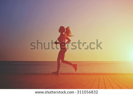 Full length silhouette of young sportswoman running on the wooden pier against ocean in beautiful evening, woman runner with good figure doing intensive fitness training of the ocean beach at sunset - stock photo