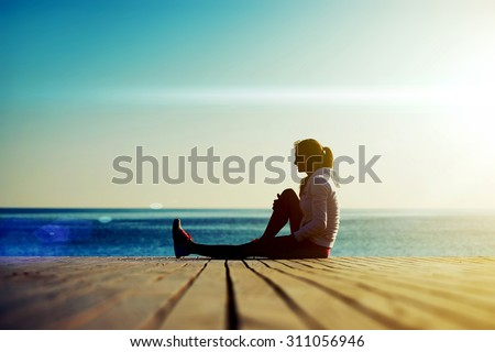 Full length silhouette of young woman runner sitting on the wooden pier against ocean while resting after an run in beautiful evening, sportswoman with good figure resting after an active run outdoors - stock photo