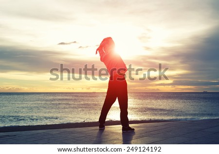 Full length silhouette portrait of a male jogger doing warm up in the morning and admiring amazing sunrise while standing next to the sea - stock photo