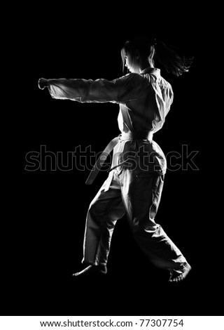 full-length silhouette portrait of beautiful martial arts girl in kimono excercising karate kata on black - stock photo