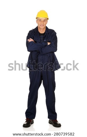 Full length smiling constructor with folded arms. - stock photo