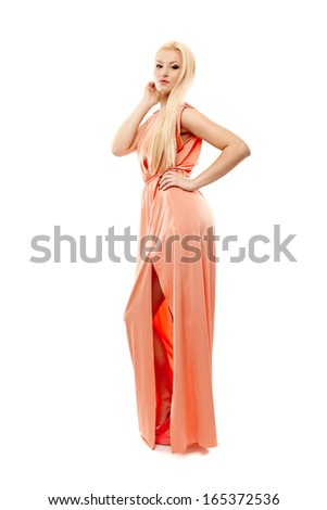 Full length studio portrait of beautiful blonde wearing long evening dress with hand on hip, isolated over white background