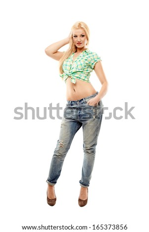 Full length studio portrait of sexy blonde wearing jeans and shirt isolated over white background