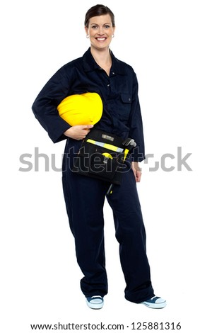 Full length studio shot of a relaxed construction worker with yellow helmet. - stock photo