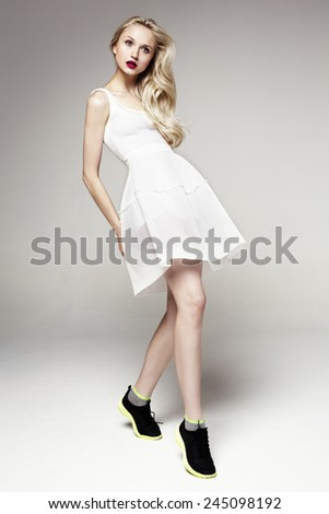 Full length studio shot of pretty model on grey background - stock photo