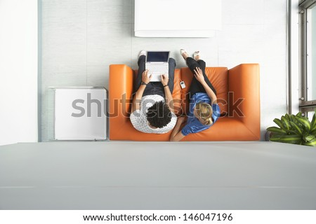 Full length top view of a man and woman using laptop on orange sofa in reception room at office - stock photo
