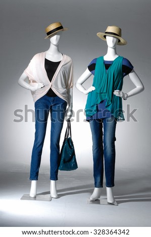 full-length two female in hat with bag on mannequin in light background - stock photo