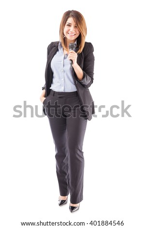 Full length view of a beautiful young successful woman giving a talk with a microphone on a white background - stock photo