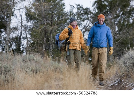 Full length view of a couple dressed in winter clothing and hiking through a wooded area. They are both smiling and walking toward the camera. Horizontal format. - stock photo