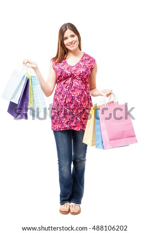 Full length view of a pretty pregnant woman doing some shopping and holding a few bags
