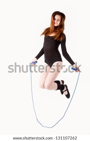 Full length view of an attractive woman with jumping rope at white background - stock photo