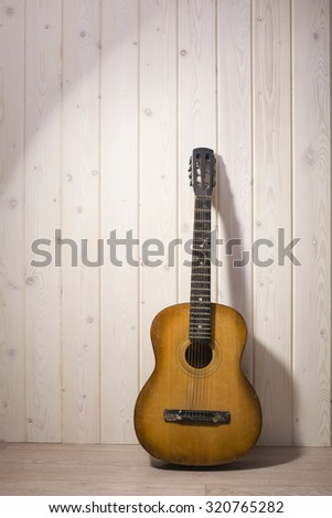 Full length view of one acoustic string light brown color wooden musical instrument of guitar with beautiful shape and fretboard indoor in studio on white wood backdrop, vertical picture