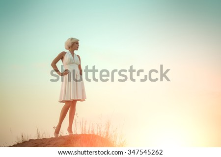 Full length view of one young beautiful fashionable retro sexy woman with blonde hair in white dress standing outdoor in sunset on sky natural background copy space, horizontal picture - stock photo