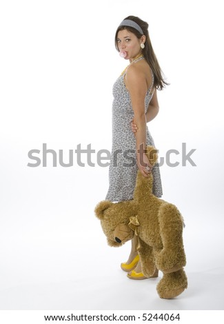 Full length view of teenage girl holding teddy bear and blowing bubble gum. - stock photo