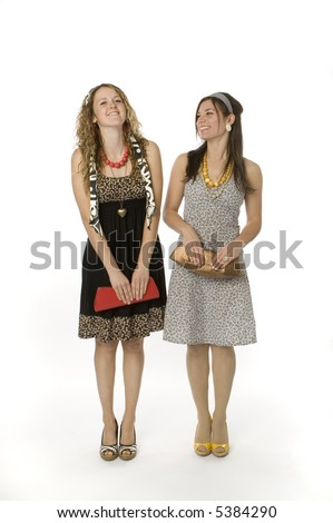 Full length view of two teenage girls standing, wearing pretty dresses. - stock photo