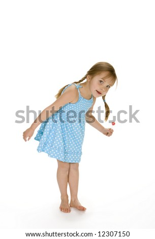 Full length view of 5 year old girl wearing blue poka dot dress. White background.