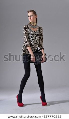 Full length Vogue style fresh beautiful fashion model with bag over light background - stock photo