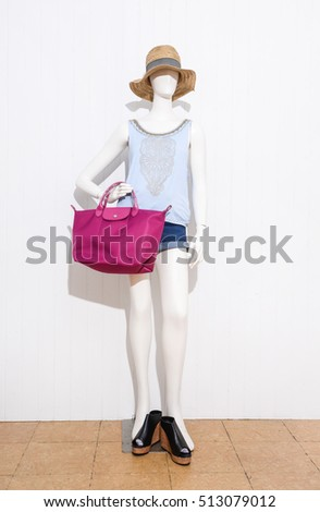 full-length White dress with hat and short jeans , bag on female mannequin-wooden background