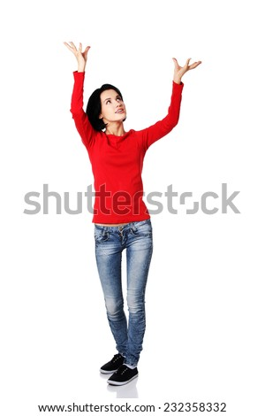Full length woman holding a copyspace up high.