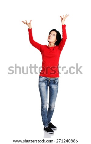 Full length woman holding a copyspace up high. - stock photo