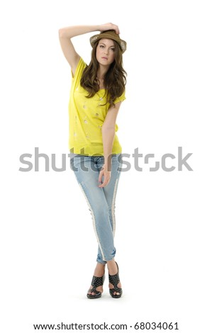 Full length woman in jeans with hat posing in the studio - stock photo