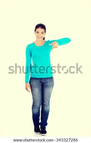 Full length woman pointing down. - stock photo
