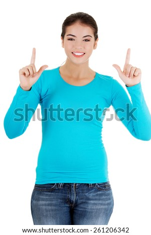 Full length woman pointing up. - stock photo