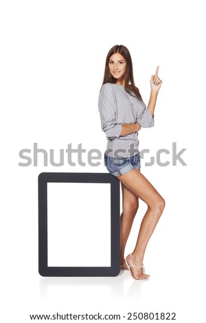 Full length woman showing blank empty screen with copy space. Happy caucasian girl standing with tablet frame and pointing finger up, over white background - stock photo