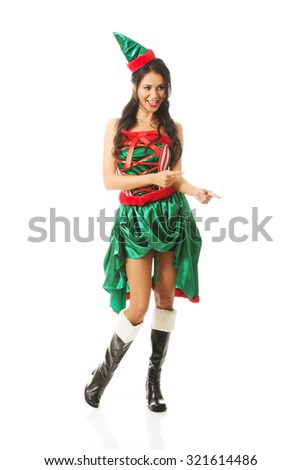 Full length woman wearing elf clothes pointing to the right. - stock photo