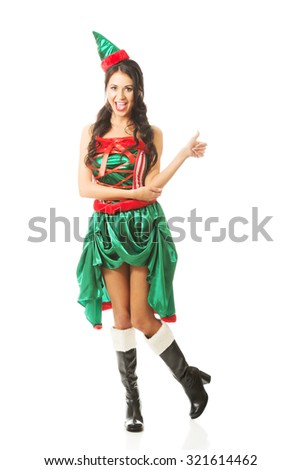 Full length woman wearing elf clothes showing thumbs up. - stock photo