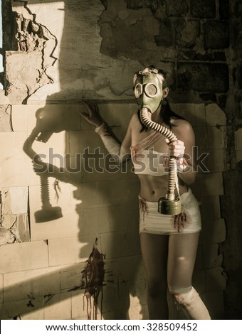 Full length Woman with gas mask in a grunge background Post apocalypse girl stand in angle abandoned dirty yellow wall with shadow from sun light Toxic trash in dusk room  - stock photo