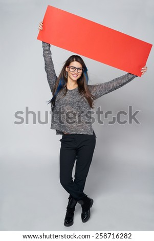 Full length young casual woman holding red blank cardboard over head, over gray background - stock photo