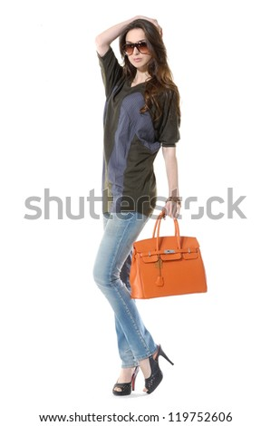 Full length young fashion women wearing sunglasses with bag on black background - stock photo