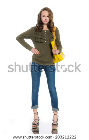 Full-length young woman in jeans with yellow bag posing - stock photo