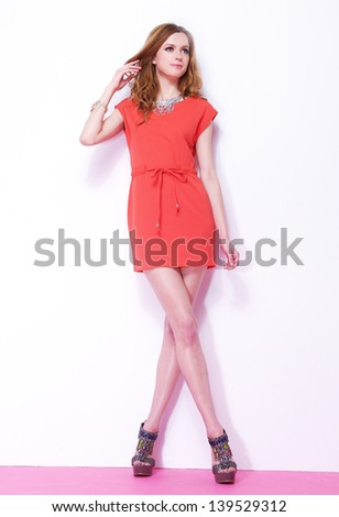 Full length young woman in red dress posing pink background - stock photo