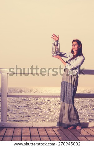 Full length young woman on pier with oil kerosene lamp. Concept carrying light, daylight - stock photo